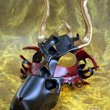 Leather dragon mask in red, black and gold.