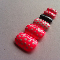 Pink and white fake nails with polka dots with black glitter accent nail