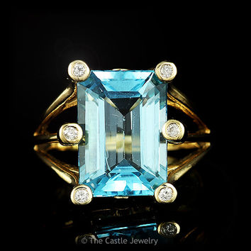 Emerald Cut Blue Topaz Ring with Bezel Set Diamond Accents in 14k Yellow Gold Triple Split Shank Mounting