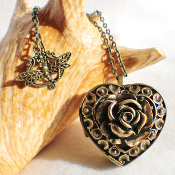 Music box locket,  heart locket with music box inside, in bronze with filigree rose adorning front cover.