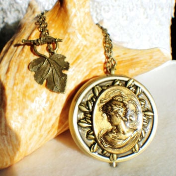 Music box locket on gold stand, round locket in bronze with Victorian maiden and bronze accents