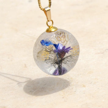 Ikebana inspired violet&blue flower arrangement in amethyst vase, secret planet pendant with layered golden rose adornments encased in resin