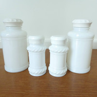Four milk glass spice jars, two large and two small