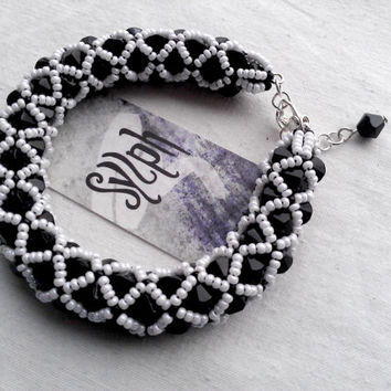 Luxurious netted bead-bracelet made out of white and black Czech 11/0 seedbeads and black bicones