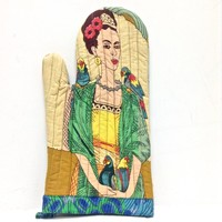 Using this iconic Frida Kahlo mitten in your kitchen when you cook, featuring Frida Kahlo Tropical Ocre print at back, Frida Kahlo & Birds print at front with a blue print colored border, quilted detailing with a layer of Insul-Brite thermal material insid