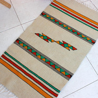 Handwoven kilim rug in white with yellow, orange and green motifs, unique handmade wool rug