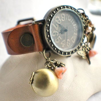 Wrist watch, in tan leather with bronze adornments, locket and freshwater pearls, and bead charms.