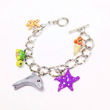 Cute Sea Life Polymer Clay Charm Bracelet including a dolphin, turtle, hermit crab and starfish charms for a marine animal collection