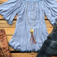 Our I Write The Songs Top is a must have! It's a off the shoulder lace trim top with tassel to the sleeves and bottom hem. Crocheted neckline.