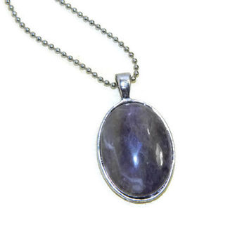 Polished purple amethyst stone oval cabochon set in silver tray with silver ball chain