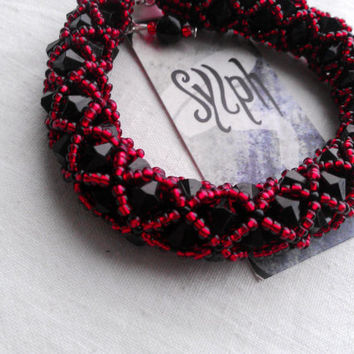 Luxurious netted bead-bracelet made out of red and black Czech 11/0 seedbeads and 6mm black bicones