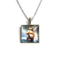 Pendant charm with glass dome.Silver colour. Ship at the sea. Marine style.