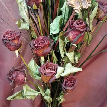 Handmade dried flowers arrangemen. beautiful red roses set in a purple tinted glass vase.