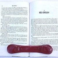 "BookBone® - Hold Books Open - Color RED - Made in USA - Weighted rubber bookmark won't slide off even when book is tilted. To see all Colors, Printed and Custom Printing options enter ""BookBone"" in the search bar above (without quotes)."