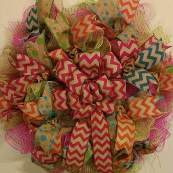"Large deco mesh ruffle wreath with chevron bow centerpiece. 29"" and 8+"" thick. Pink, green and natural jute mesh."