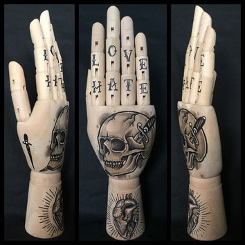 Wooden hand mannequin with original drawings of a skull and dagger and an anatomical heart 'tattoo style'