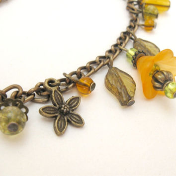Bronze charm bracelet, amber yellow flowers and green leaves