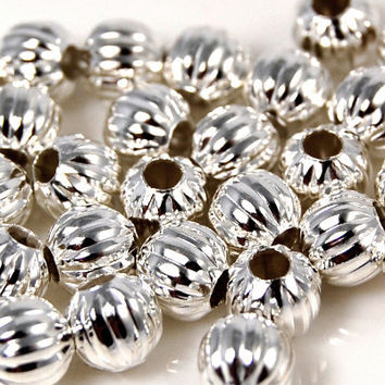 Silver, 6mm corrugated round. Sold per pkg of 100