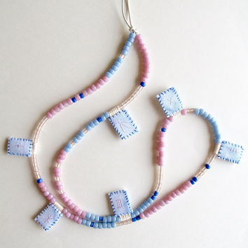 Asymmetrical long necklace with hand embroidered shibori dyed pendants on long silver leather cord with pink and blue glass beads