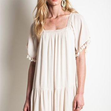 This gauze relax fit dress features a crinkle blended cotton fabric, square neckline with crochet detailing, oversize sleeve with fringe tassel design, and tiered ruffle at bottom of skirt. Unlined. Pair with open toe strappy tan sandals.