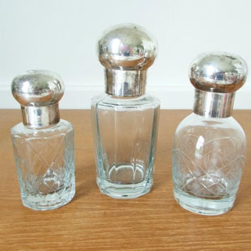 Decorative cut glass bottles with silver plated lids, set of three