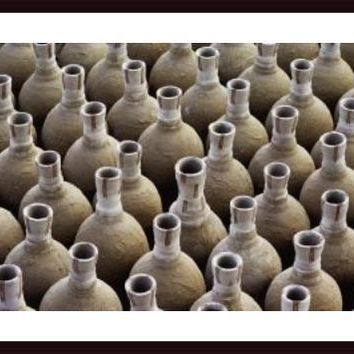 Newly made clay vases are lined up, awaiting to be cooked in a kiln., framed black wood, white matte