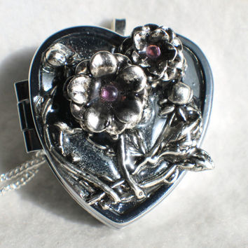 Music box locket,  heart shaped  locket with music box inside, in silver with 3-D silver flower spray on cover.