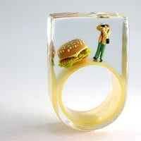Burger shooting – Sensational figure ring with a mini-photographer and hamburger on a golden colored ring made of resin for a photo shooting