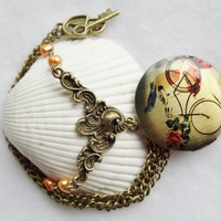 Round locket with bicycle and bird on front cover adorned with peach fresh water pearls and bronze accents