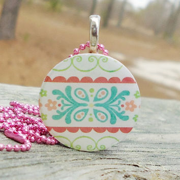 Round Patterned Necklace with Pretty Flowers Pastel Colors on Wood Tile