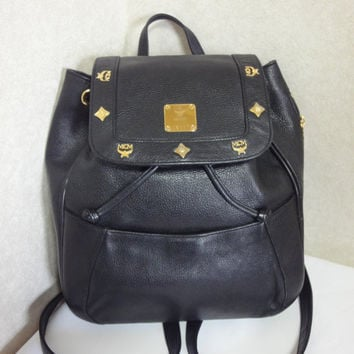80's vintage MCM genuine leather black backpack with gold tone hardware and charms. Unisex bag for daily use.