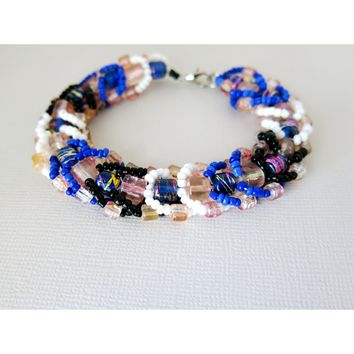 A crackling surprise party blue peach white black woven flat spiral seed bead bracelet