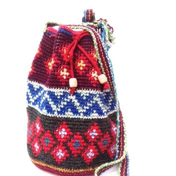 "This boho/hippie chic style hand made drawstring bucket bag features a textured feel native Pattern throughout, adjustable drawstring closured with wooden beaded detailing, and self-tie adjustable shoulder with a 23"" drop."