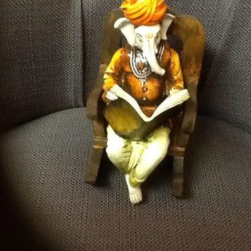Lord Ganesh on a Rocking chair reading New paper