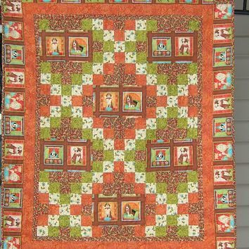 Crib Size Quilt in orange, brown, green and cream featuring puppies