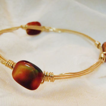 Dark Red and Yellow Glass Swirl Beads on Wire Wrapped Bangle -  glass swirl bead on gold tone wire