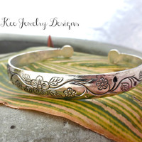 Floral Silver metal cuff with adjustable closure. 1/2 inch wide.