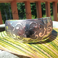 Floral  Silver metal cuff with adjustable closure.