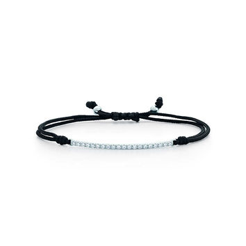 Tiffany & Co. - Tiffany Metro bar bracelet of diamonds in 18k white gold on a black cord.