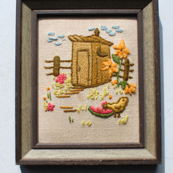 Vintage embroidered farm scene with outhouse, chicken, fence, flowers, clouds, and watermelon. The frame is rustic brown wood. Bathroom art
