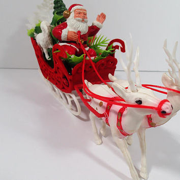 Vintage Christmas Santa Clause driving a kitsch red flocked plastic sleigh pulled by 2  Reindeer and loaded with presents, tree and lamb