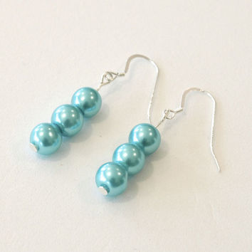 Earrings made from sky blue colored glass pearls on silver wires.