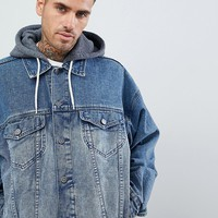 ASOS DESIGN oversized denim jacket with jersey hood in mid wash at asos.com