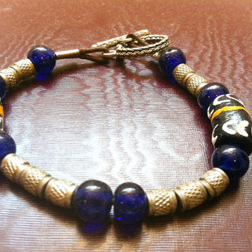 Masculine tribal bracelet with indigo blue African ceramic and glass beads with sterling silver toggle closure on leather string.