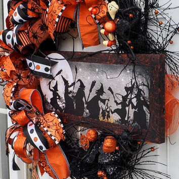 Whimsical Halloween wreath with lighted starts and burning fire under caldron.