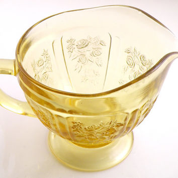 Yellow or pale amber depression glass creamer jug. Probably a federal piece in the rose of Sharon pattern.