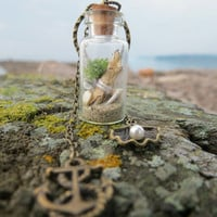 Tiny glass bottle with REAL miniature seashells, REAL sand, REAL corals, real moss and two charms.Bronze or silver. Gift and a cute box.