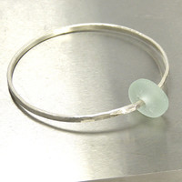 Handmade sterling silver bangle with a free flowing pale blue sea glass charm.