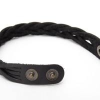 Thin handmade bracelet woven of black genuine leather with metal studs