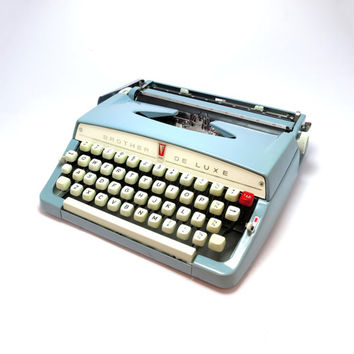 1960s Baby Blue Brother Deluxe Typewriter. In Good Condition. Includes Working Black/Red Ribbon.